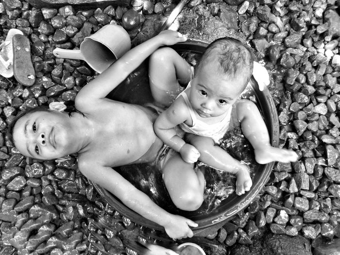 High Angle Portrait Of Siblings In Tub On Rocks