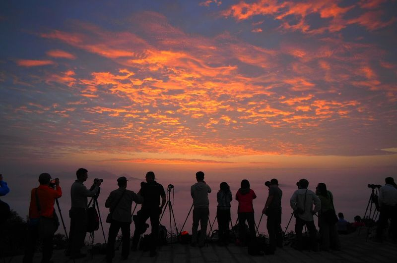 Silhouette of people taking photographs at sunset