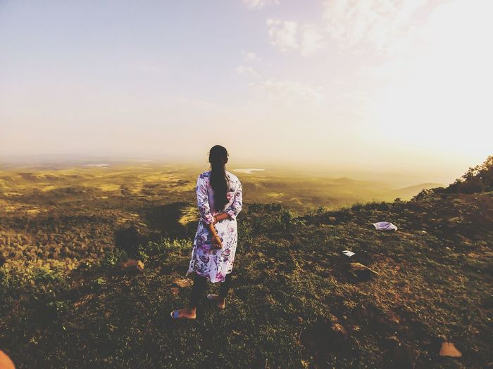 Rear view of woman standing on land against sky during sunset