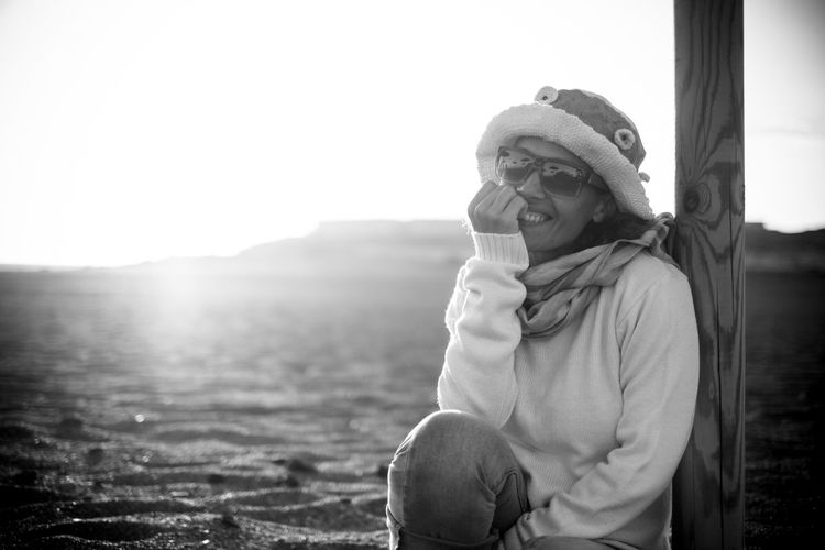 Portrait of happy woman sitting at beach against sky