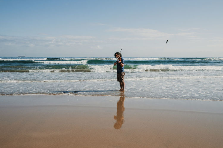 Full length of man playing violin standing on beach against sky