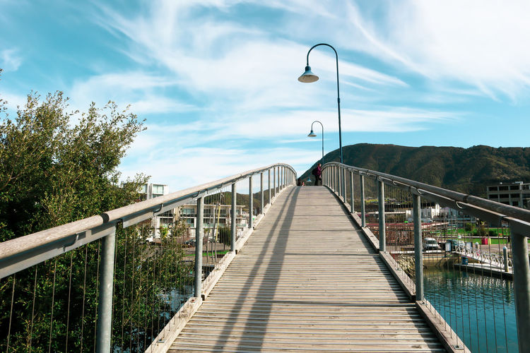 Footbridge over street against sky