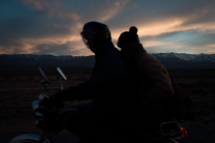 People riding motorcycle on mountain during sunset