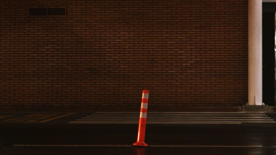 Traffic cone on road against brick wall