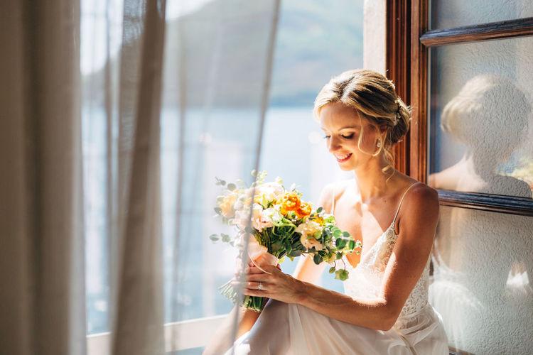Woman holding flower vase against window