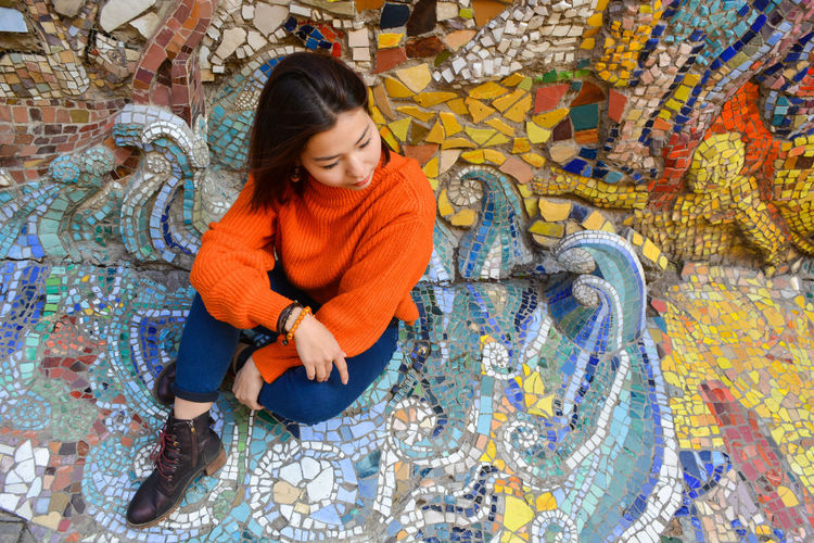 High angle view of woman sitting on mosaic