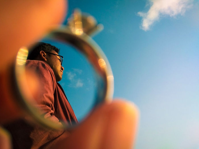 Low angle view of man seen through ring against sky