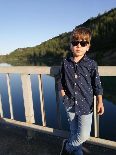 Portrait of cute boy standing by lake