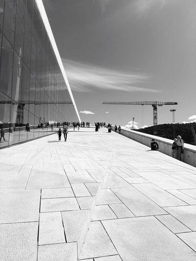 People walking at oslo opera house against sky