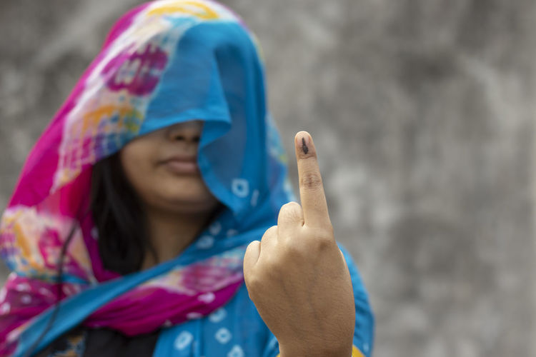 Selective focus on ink-marked finger of an indian village woman behind veil with smiling face