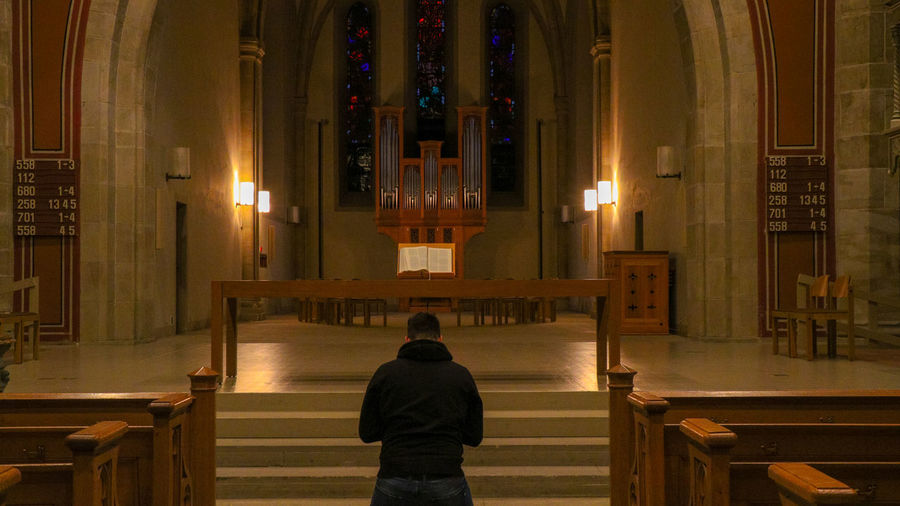 Rear View Of Man Praying In Illuminated Church