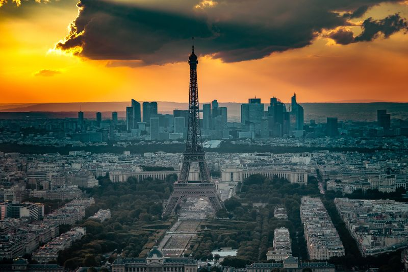 Aerial view of eiffel tower amidst cityscape during sunset