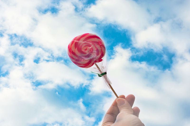 cloud with light sky light Body Part Cloud - Sky Day Directly Below Finger Hand Holding Human Body Part Human Finger Human Hand Human Limb Lollipop Nature One Person Outdoors Personal Perspective Real People Red Sky Temptation Unrecognizable Person