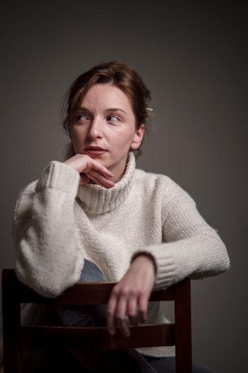 Portrait of mid adult man sitting against black background