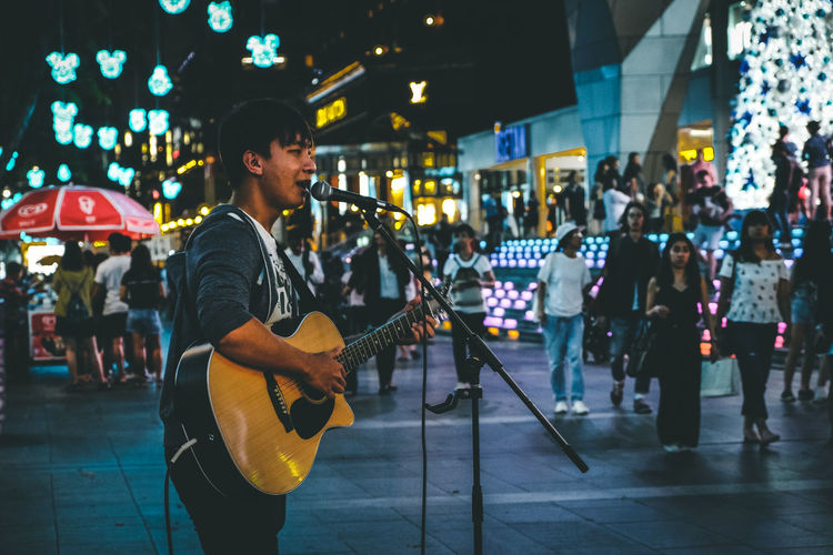 Singing for life Plucking An Instrument Artist Playing Illuminated Street Musician Men Real People Performance Arts Culture And Entertainment Incidental People Musical Equipment Street Street Performer Focus On Foreground Musician Night Music City String Instrument Guitar Musical Instrument
