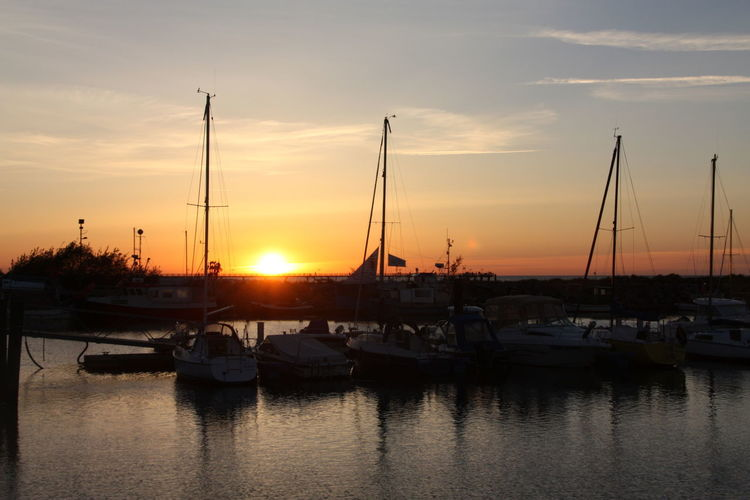 Boats moored at harbor against sky during sunset
