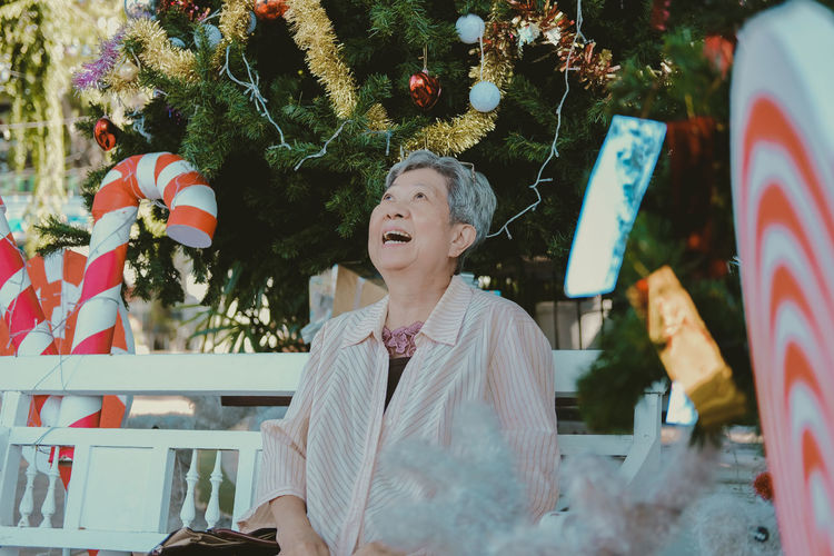 Cheerful senior woman sitting against christmas tree