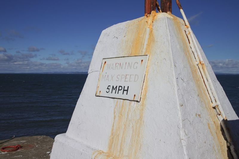 Close-up of information sign by sea against sky