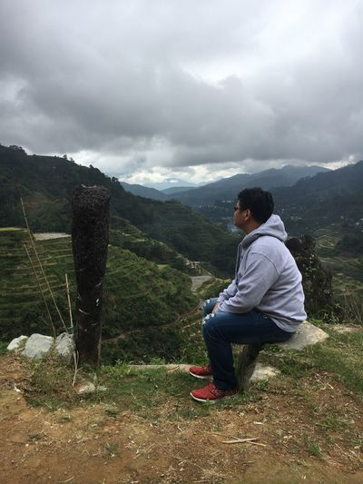 side view of man sitting on the scenic Banaue Rice Terraces view point Rubber Shoes Jeans Jacket Gray Jacket Banaue Terraced Field Terraced Field Banaue View Point Banaue Rice Terraces Casual Clothing Leisure Activity Sitting Landscape Mountain Range Young Adult Beauty In Nature