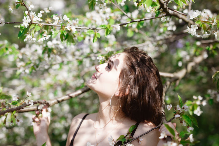 Young woman amidst flowering tree