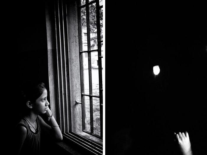 Portrait of man looking through window at night