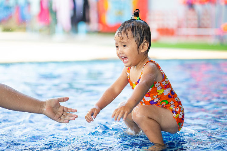 Cute girl crouching in swimming pool at water park