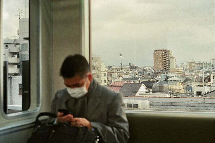 Man looking at cityscape seen through glass window