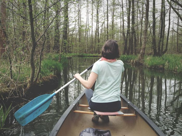 Woman Paddling Canoe On River