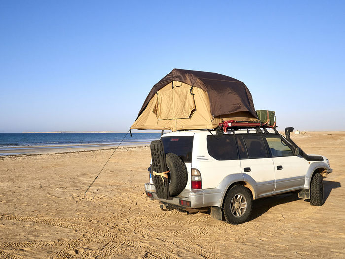 Rear view of vehicle on beach against clear sky