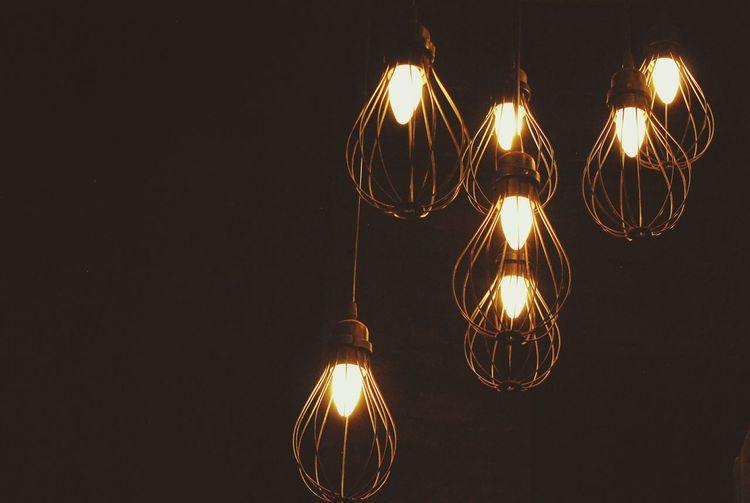 Illuminated Lighting Equipment Hanging Against Black Background