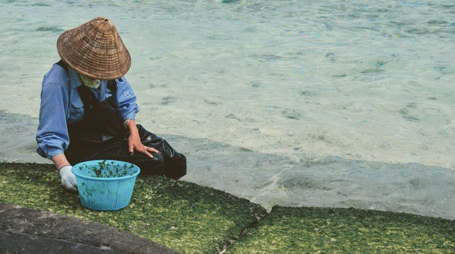 Adult Collecting Collecting Seaweed Day Everyday Lives Hat Kouri-jima Nature Obachan One Person Outdoors People Real People Sea Seashore Sitting Straw Hat Water Working Working おばちゃん 沖縄