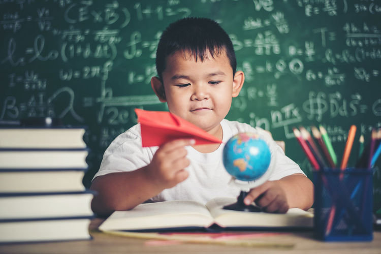 Cute boy studying at table against blackboard