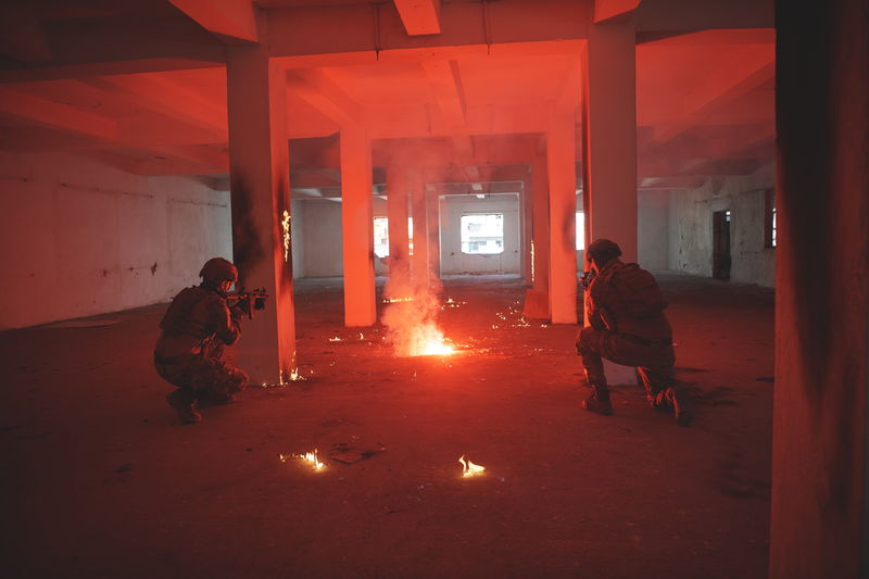 Rear view of soldiers in building with burning flares