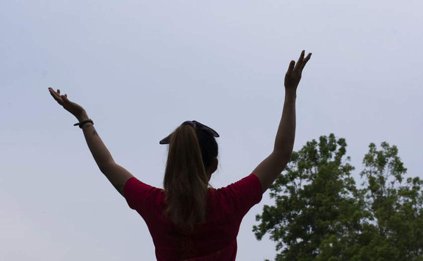 Rear view of woman with arms raised standing against clear sky