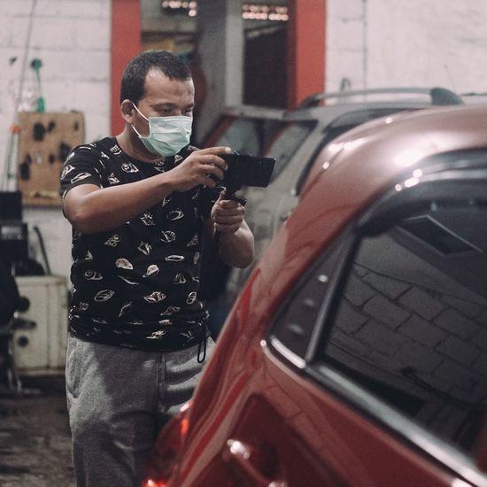 Man wearing mask photographing car