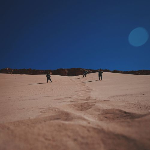 People standing in desert against clear sky