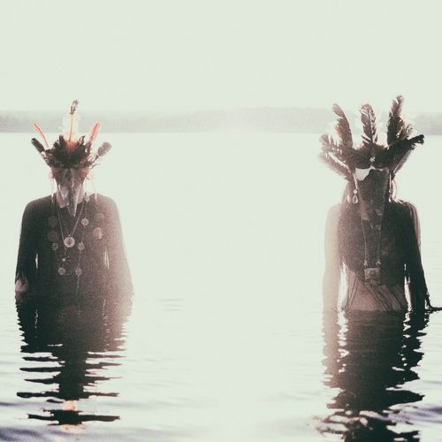 Indigenous people wearing costume while standing in lake