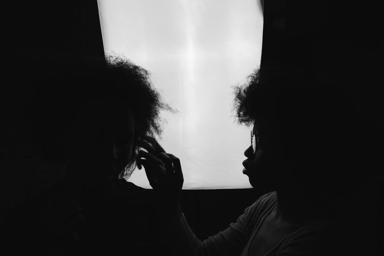 Close-up of women against window in darkroom