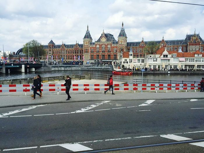 People walking on road by amsterdam centraal railway station against cloudy sky