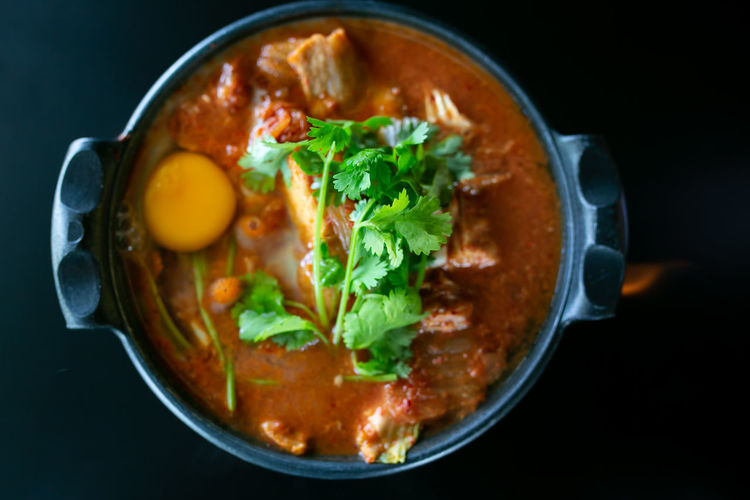 Kimchi soup with raw chicken eggs and white tofu, popular korean food.