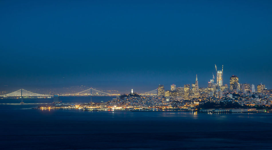 Illuminated city by sea against clear blue sky at night
