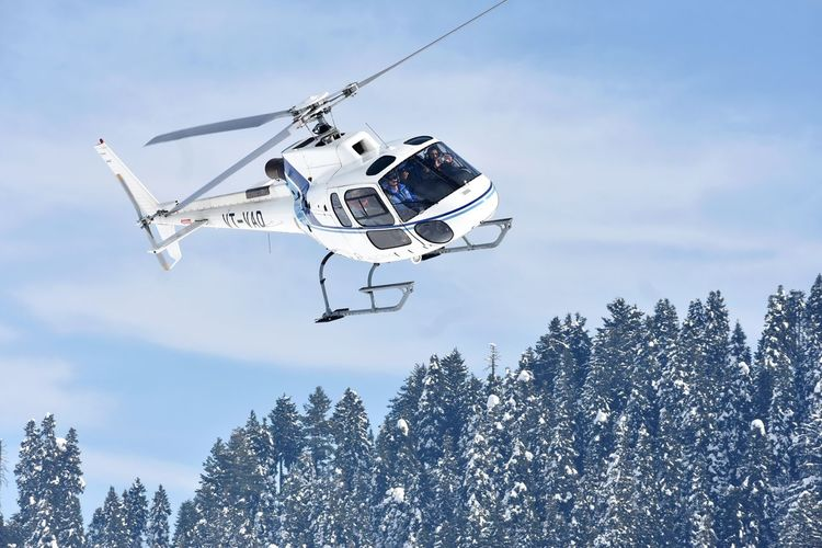 A chopper carrying tourists to the higher reaches at Gulmarg takes off during sunshine on Monday Helicopter Gulmarq Winter Tourists Gulmarq Enjoy Kashmir Tree Flying
