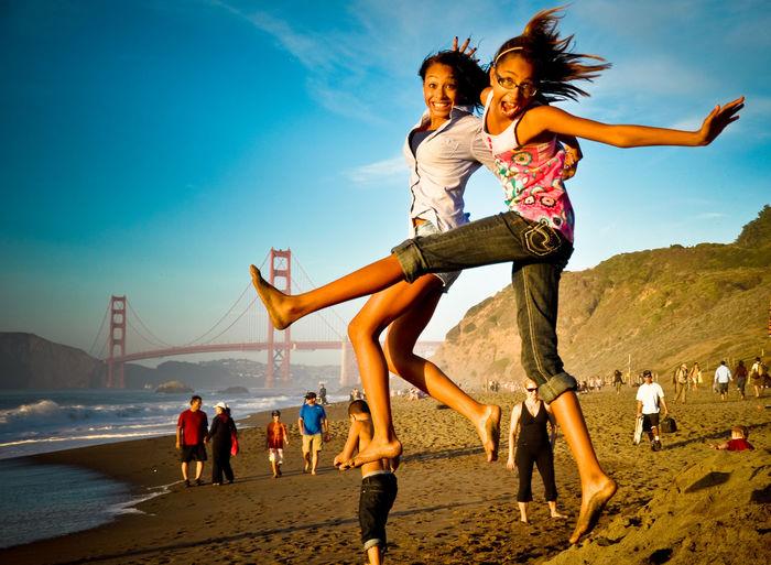 Siblings in mid-air at beach against blue sky