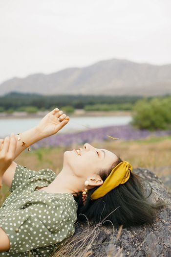 Portrait of young woman relaxing on land against sky