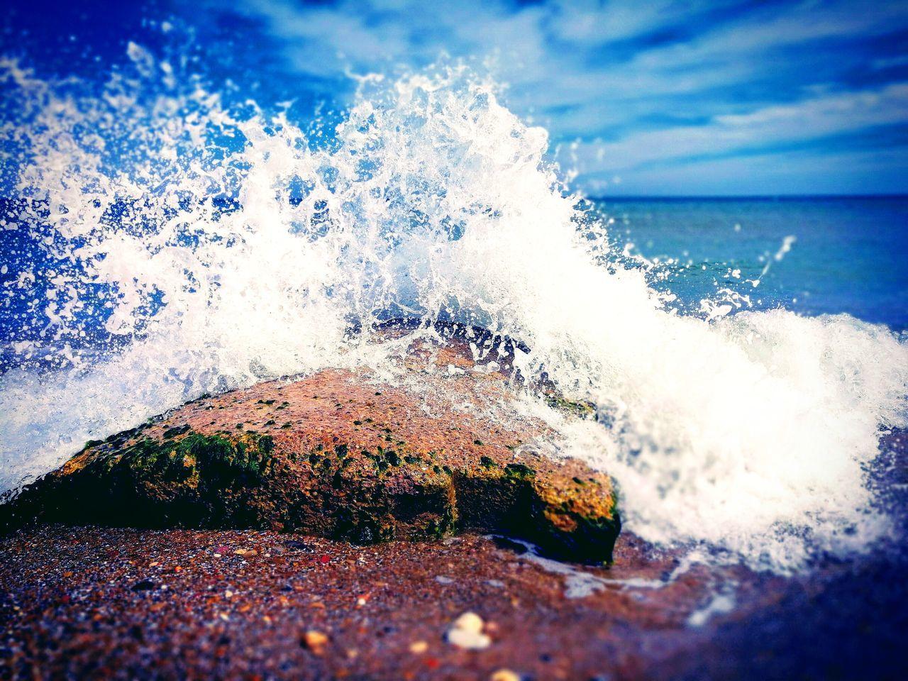 WAVES SPLASHING ON SHORE AT BEACH