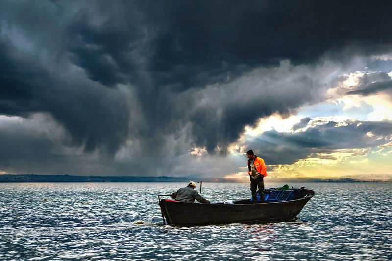 People on boat in sea against dramatic sky