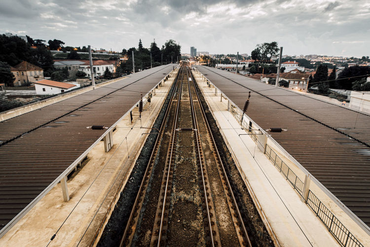 High angle view of railroad tracks by buildings against sky