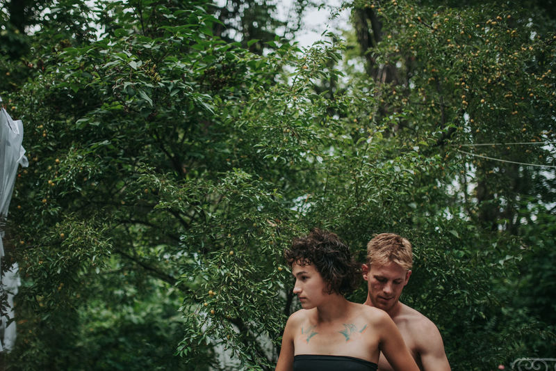 Portrait of shirtless man with woman against trees