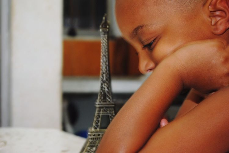 Close-up of boy by replica eiffel tower on table at home