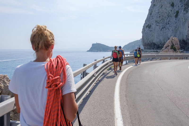Rear view of people walking on road by sea against sky